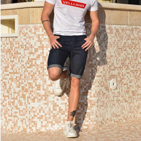 ragazzo in posa che indossa una t-shirt bianca della vellusar e un paio di bermuda in jeans con risvolto e tasche a filetto